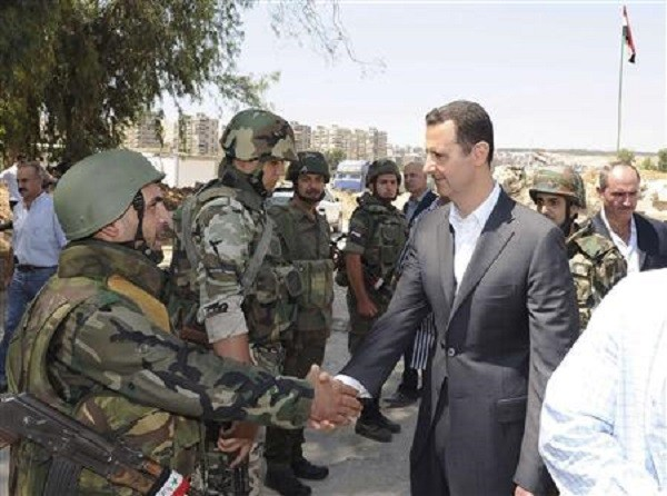 Syria's President Bashar al-Assad (R) shakes hands with a member of a military personnel.