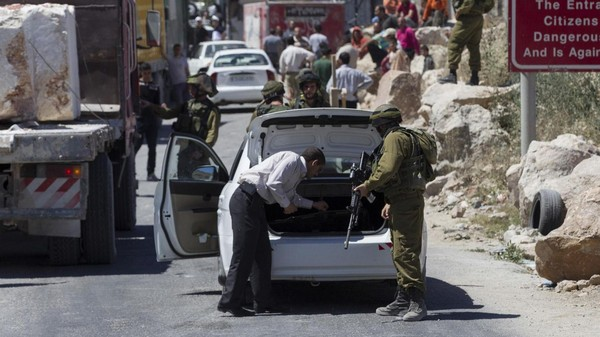An Israeli soldier searches a Palestinian vehicle at a checkpoint near Hebron