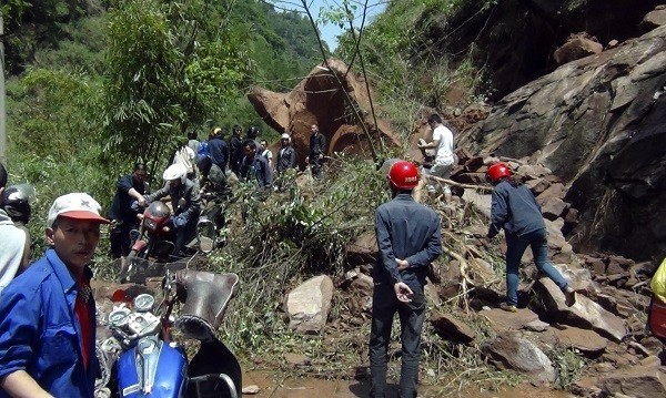 Rescuers try to remove rocks blocking a road after a strong earthquake of 6.6 magnitude hit Lushan county.