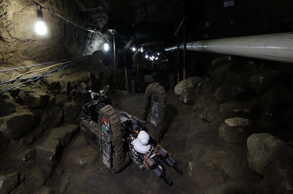 A worker from the National Institute of Anthropology and History walks next to a robot used to explore ruins on the entrance of a tunnel