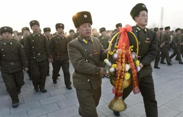 North Korean soldiers offer flowers to bronze statues (not pictured) of North Korea's late founder Kim Il Sung and late leader Kim Jong Il at Mansudae in Pyongyang, in this picture taken and provided by Kyodo December 17, 2013, to mark the second death anniversary of Kim Jong Il