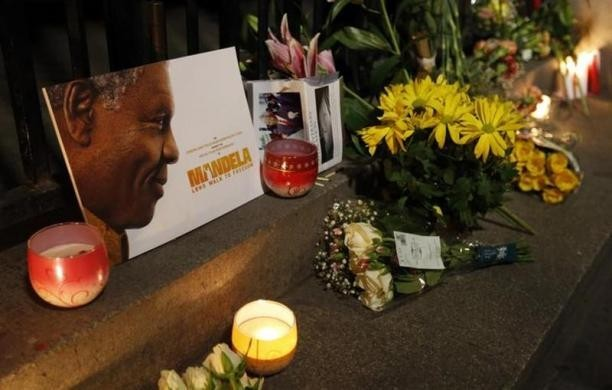 Flowers, candles and tributes are left in memory of Nelson Mandela outside the South African High Commission across from Trafalgar Square in London