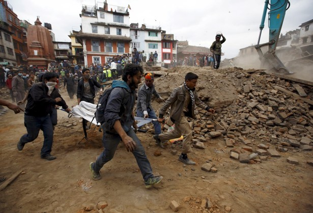 People carry the body of a victim on a stretcher, which was trapped in the debris after an earthquake hit, in Kathmandu, Nepal April 25, 2015.
