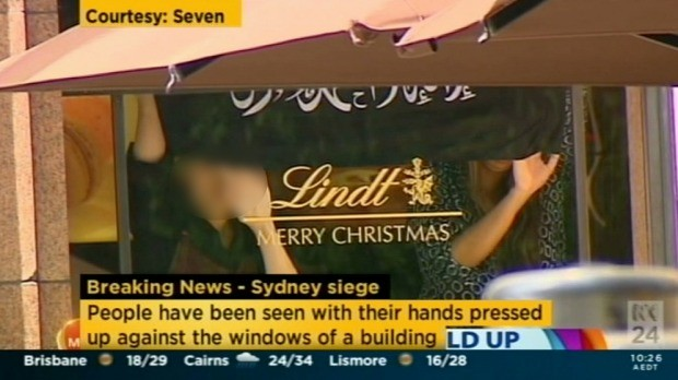 Hostages at the Lindt Cafe hold the Black flag.