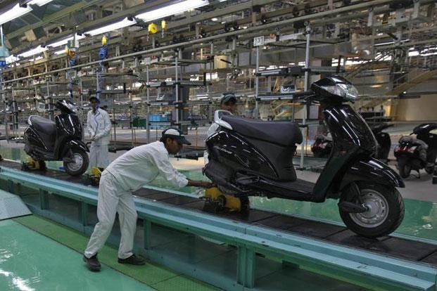 Employees work at an assembly line of Activa scooter at Honda Motorcycle and Scooter India Pvt. Ltd. plant in Tapukara, Rajasthan.