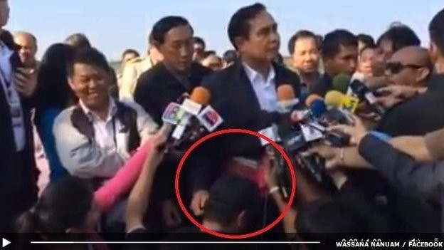 Thailand's new PM, General Prayuth Chan-Ocha is seen stroking the head of a journalist and gently tugging his right ear in camera.