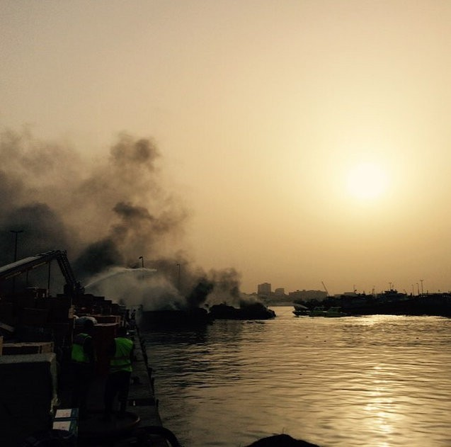 Fire engines spray water on the remains of two boats that were destroyed in an inferno on Monday afternoon.