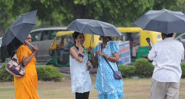 People enjoy themselves during rains in New Delhi.