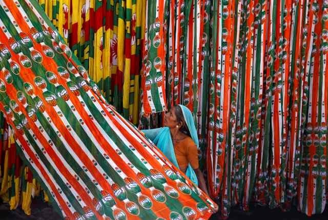 A worker pulls a roll of flags of India's ruling Congress party, kept for drying at a flag manufacturing factory, ahead of the 2014 general elections