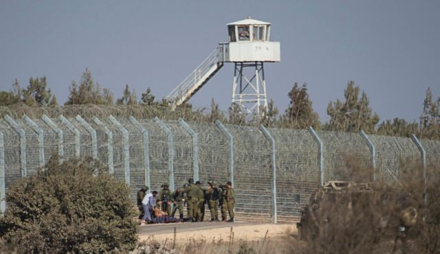 Israeli soldiers stand near the border with Syria in the occupied Golan Heights as they prepare to evacuate a wounded Syrian
