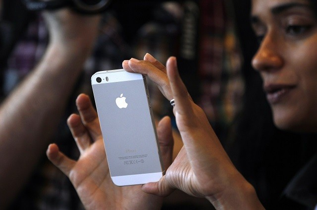 A Woman Tries the Silver Colored Version of the New iPhone 5S After Apple Inc's Media Event in Cupertino, California