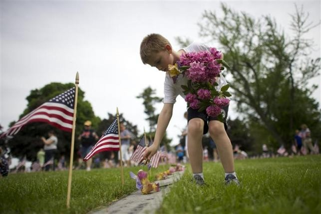 Alex Teeter, 8, places flowers on the grave sites of Battle of Gettysburg soldiers during a ceremony at National Soldier's Cemetery following the Gettysburg Memorial Day parade in Gettysburg, Pennsylvania, May 26, 2014.