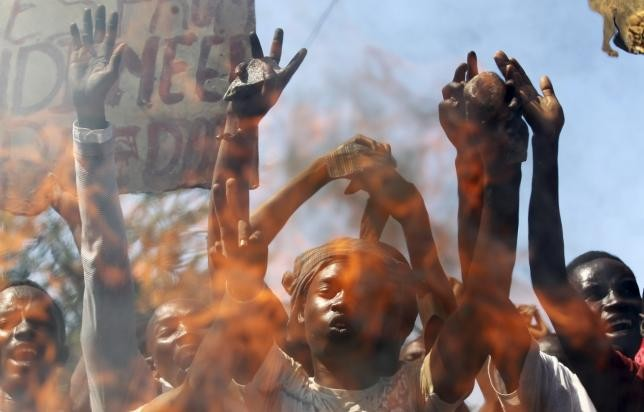 Protesters are seen behind a fire barricade as they chant anti-government slogans before clashing with riot police in Burundi's capital Bujumbura, April 28, 2015.