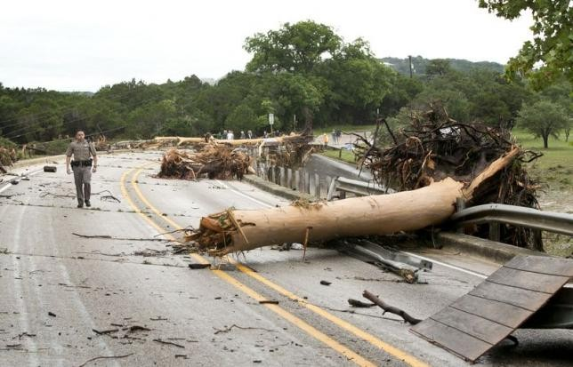 Department of Public Safety Trooper Marcus Gonzales walks on the Highway 12 bridge over the Blanco River which was blocked by large trees after flooding in Wimberly, Texas, United States May 24, 2015.