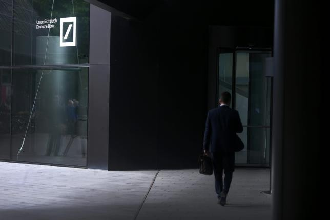 The headquarters of the Deutsche Bank are reflected in the polished floor, in Frankfurt, Germany, April 27, 2015.