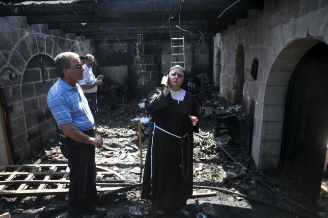 A nun stands at the scene of a fire in the Church of Loaves and Fishes on the shores of the Sea of Galilee in northern Israel June 18, 2015.