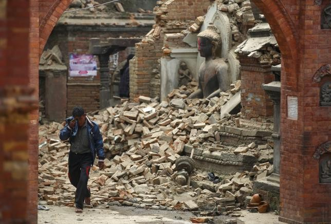 A man cries as he walks on the street while passing through a damaged statue of Lord Buddha a day after an earthquake in Bhaktapur, Nepal April 26, 2015.