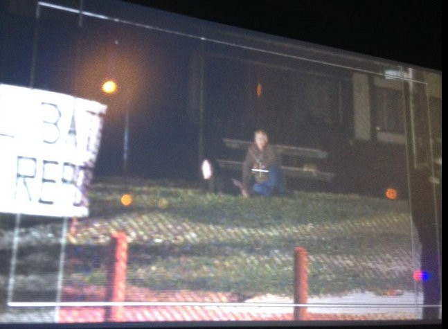 A camera footage shows a man in black hood lying on the ground, while a middle-aged man strapped with explosives sitting cross legged.