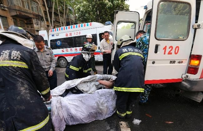 Rescuers move an injured person into an ambulance from the site of a hotel fire in Xiangyang, Hubei province, April 14, 2013. At least 11 people have been confirmed dead and 50 others injured in the fire on Sunday morning,