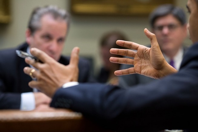 President Barack Obama gestures during a meeting in the Roosevelt Room of the White House, Dec. 18, 2013.