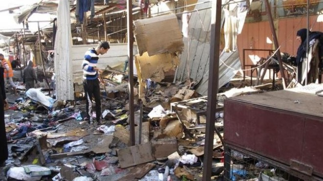 People stand among debris at the site of a bomb attack at a marketplace in Baghdad's Doura District December 25, 2013.