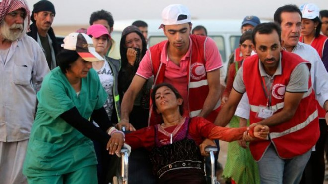 Members of the Kurdish Red Crescent helping a Yazidi woman