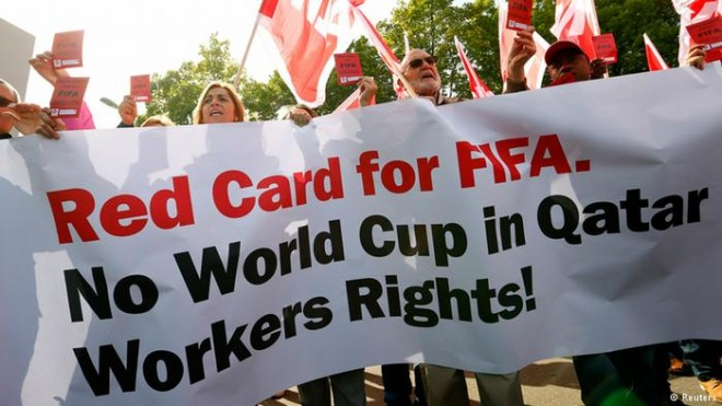 Members of the Swiss UNIA workers union display red cards and shout slogans during a protest