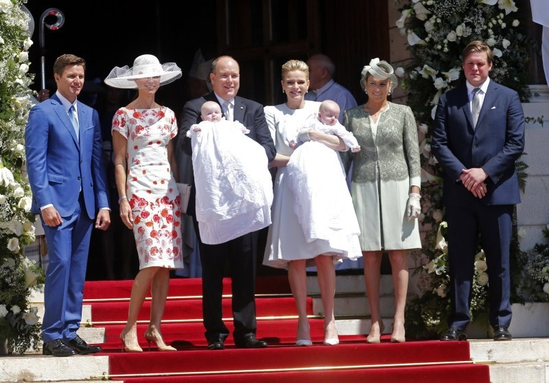 Prince Albert II of Monaco and his wife Princess Charlene hold their twins Prince Jacques (R) and Princess Gabriella (L) as they pose with godmothers and godfathers while leaving Monaco's Cathedral after their christening ceremony