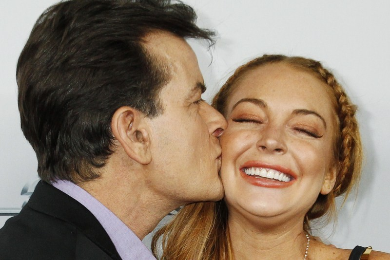 Cast member Charlie Sheen kisses co-star Lindsay Lohan on the cheek as they pose at the premiere of their new movie 'Scary Movie 5' in Hollywood