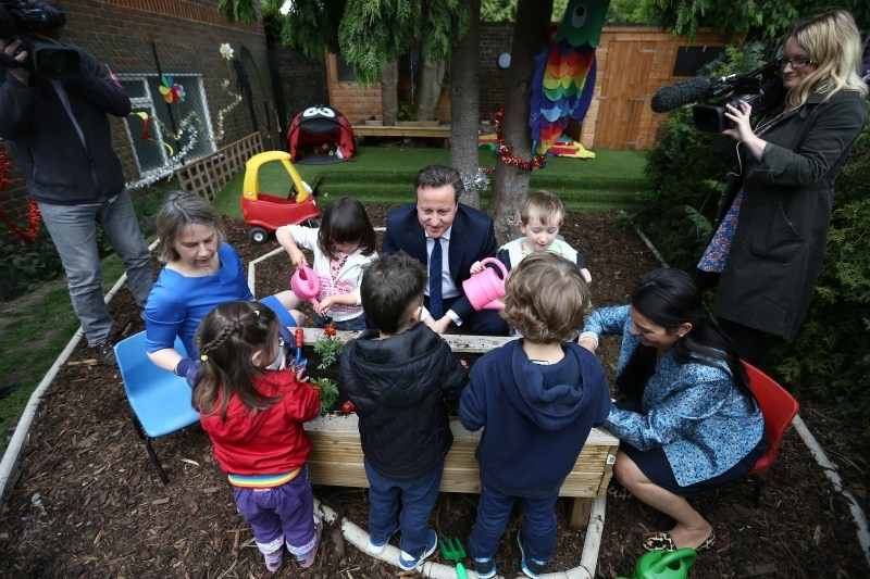 Britain's Prime Minister David Cameron plants flowers with children during a visit to a children's nursery in London
