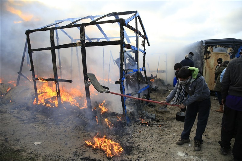 Clashes break out in Calais as police clear part of the shanty town in northern France.
