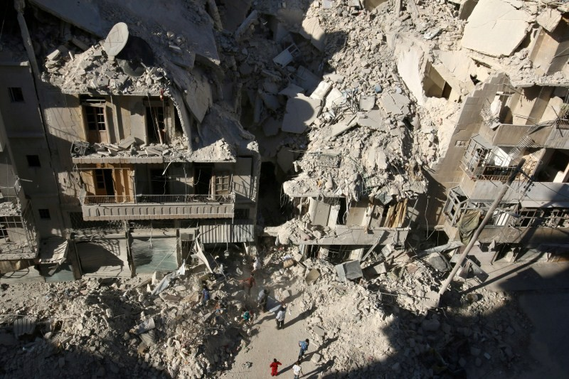 People dig in the rubble in an ongoing search for survivors at a site hit previously by an airstrike in the rebel-held Tariq al-Bab neighborhood of Aleppo.