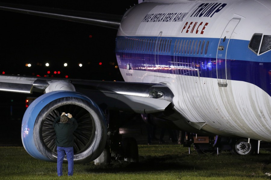A man takes a photographs as he inspects a campaign plane that had been carrying U.S. Republican vice presidential nominee Mike Pence after it skidded off the runway while landing in the rain at LaGuardia Airport in New York, U.S.