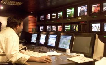 A news producer sits inside a news studio