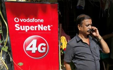 A man speaks on his mobile phone next to a Vodafone advertisement in Kolkata