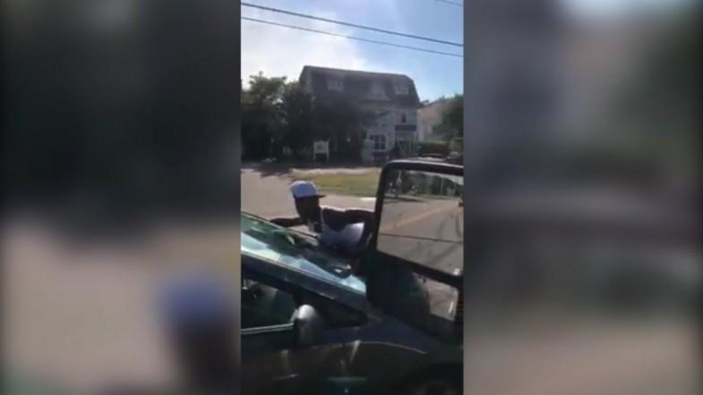 Woman clings onto car in bizarre traffic incident