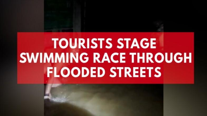 Tourists stage swimming race through flooded street