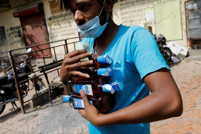 FILE PHOTO: A man carries liquor bottles after buying them at a wine shop during an extended nationwide lockdown to slow the spread of the coronavirus disease (COVID-19), in New Delhi, India, May 4, 2020. REUTERS/Adnan Abidi/File Photo