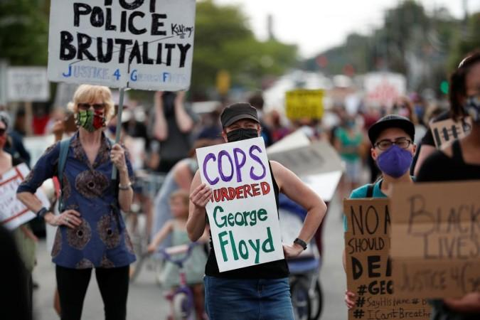 Protesters gather at the scene where George Floyd, an unarmed black man, was pinned down by a police officer kneeling on his neck before later dying in hospital in Minneapolis, Minnesota, U.S. May 26, 2020. REUTERS/Eric Miller