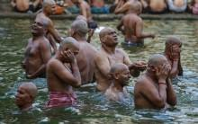 Hindu devotees pray in a holy pond on the auspicious day of Mahalaya in Mumbai, India, on 12 October 2015. Hindus offer prayers with holy water after taking a dip in the river to honor the souls of their departed ancestors during Mahalaya, which is also called Shraadh or Pitru Paksha.