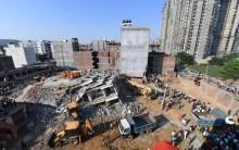 """At least three persons have died in a twin-building collapse in Uttar Pradesh's Greater Noida area, police said on Wednesday. The incident in Shahberi village took place late on Tuesday, apparently due to """"too much moisture in the walls of the basement and poor construction material used"""", an official told IANS. Three persons, including the builder Ganga Prasad Dwivedi have been taken into custody, he added. There were a dozen families living in the two buildings and it is feared that more than 50 persons, including labourers were still buried under the debris. The National Disaster Response Force (NDRF) teams that had reached the spot immediately have pulled out three bodies from the rubble so far, the official added."""
